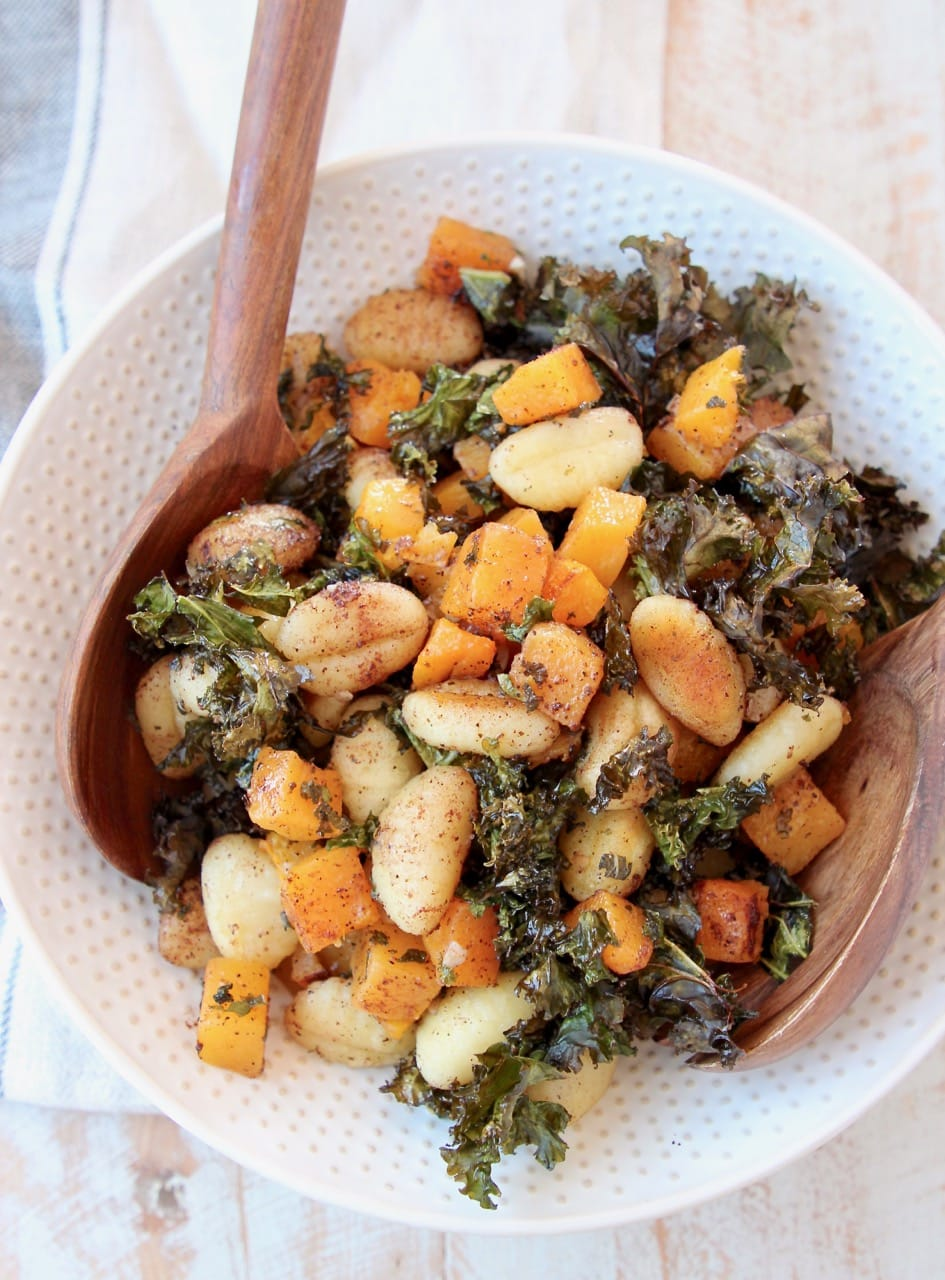 Gnocchi, butternut squash and kale in large white bowl with wooden serving spoons