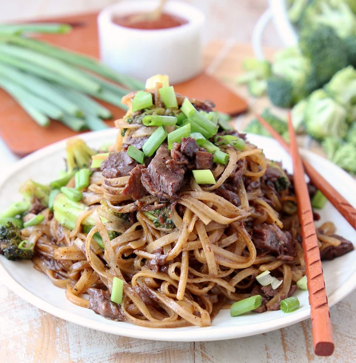 Black Pepper Beef and Brocolli with Rice Noodles and Scallions on plate with wood chopsticks