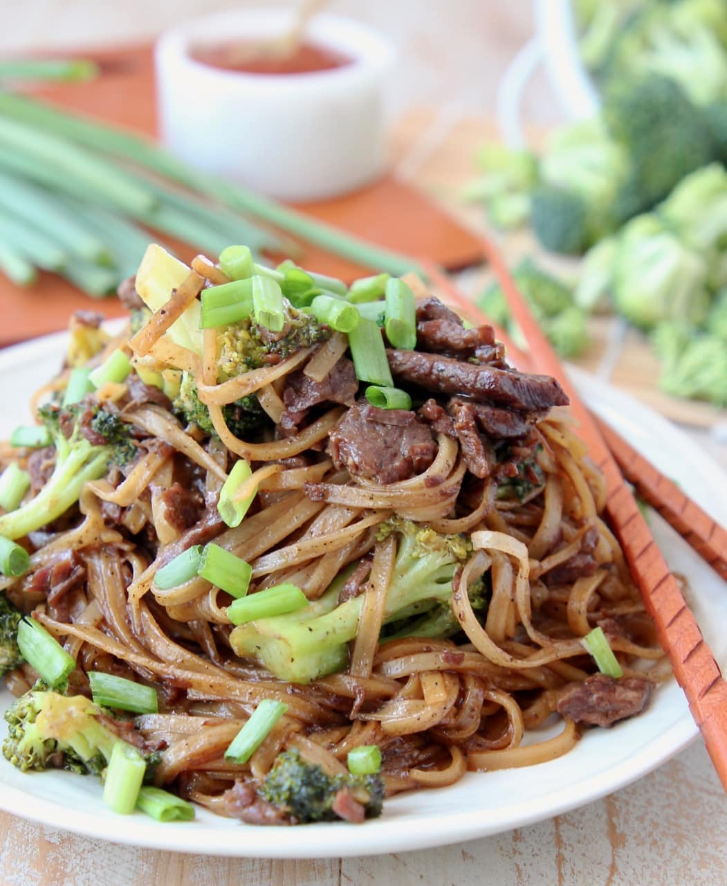 Black pepper beef and rice noodles with scallions on plate with wood chopsticks