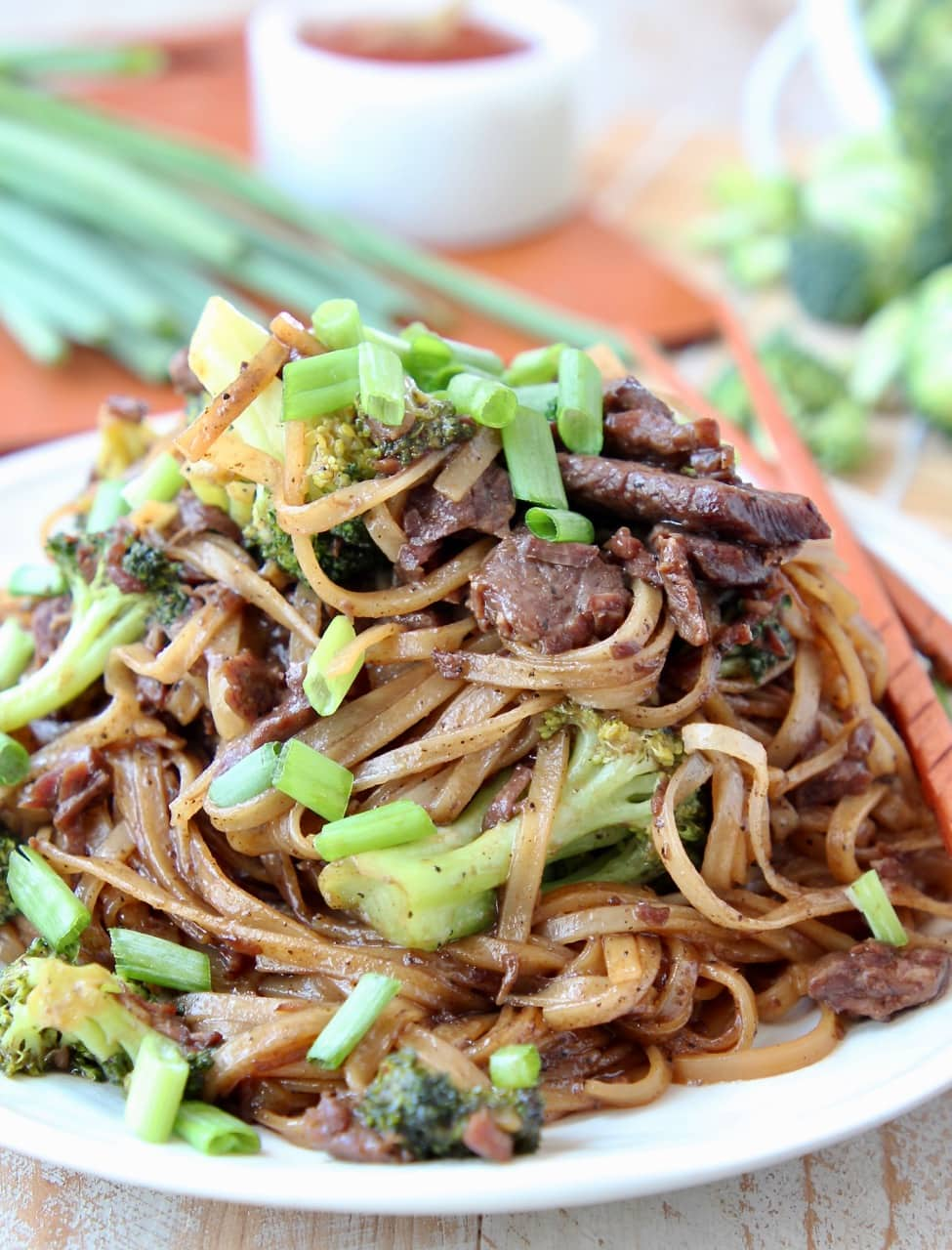 Black Pepper Beef and Broccoli with rice noodles and scallions on plate with chopsticks