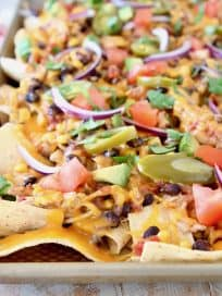 Chicken nachos on baking sheet with jalapenos, tomatoes, cheese, black beans and red onions, sitting on red and white striped towel