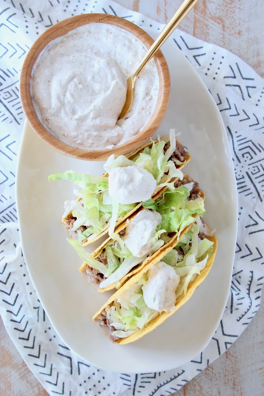 Ground beef tacos in crispy shell with shredded lettuce and french onion dip on plate with bowl of french onion dip with gold spoon