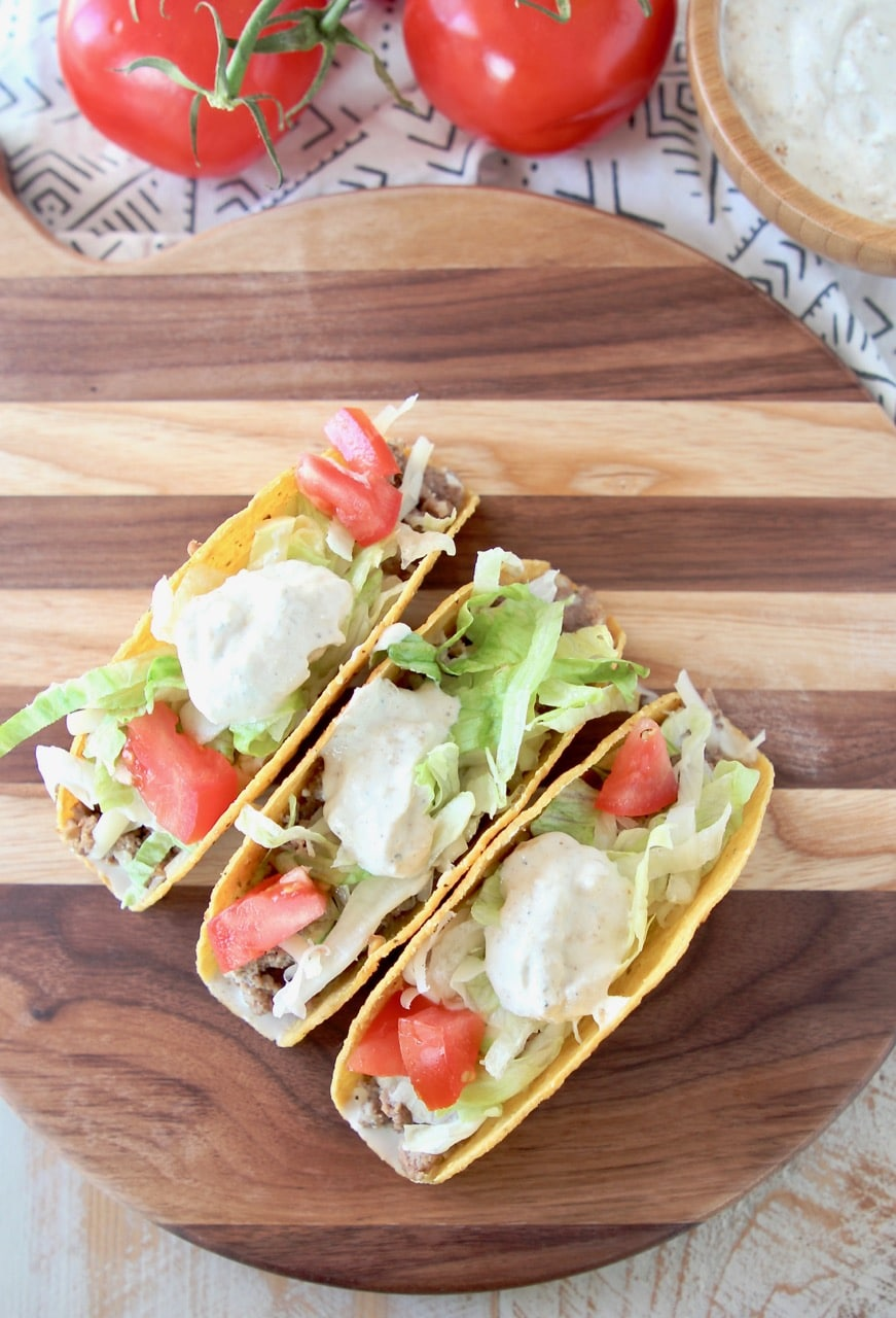Crispy shell ground beef tacos on wood cutting board with tomatoes and french onion dip