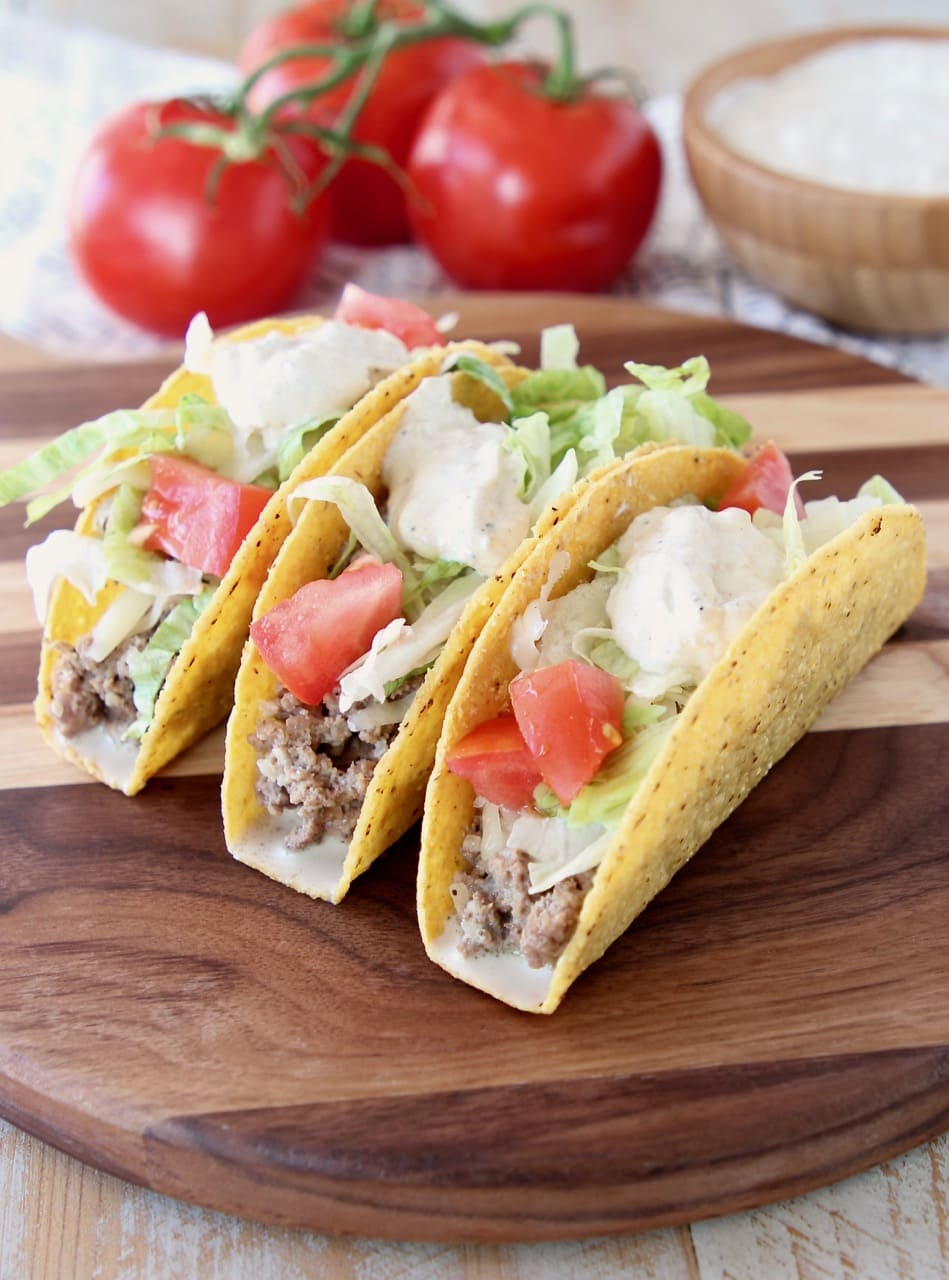 Ground beef tacos in crispy shells with french onion dip, diced tomatoes and shredded lettuce on wood cutting board with tomatoes on the vine and bowl of french onion dip