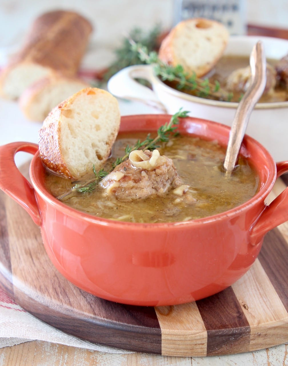 French onion meatball soup in orange crock with fresh spring of thyme on top and copper spoon in the soup with a slice of bread on the side, sitting on a wood striped cutting board