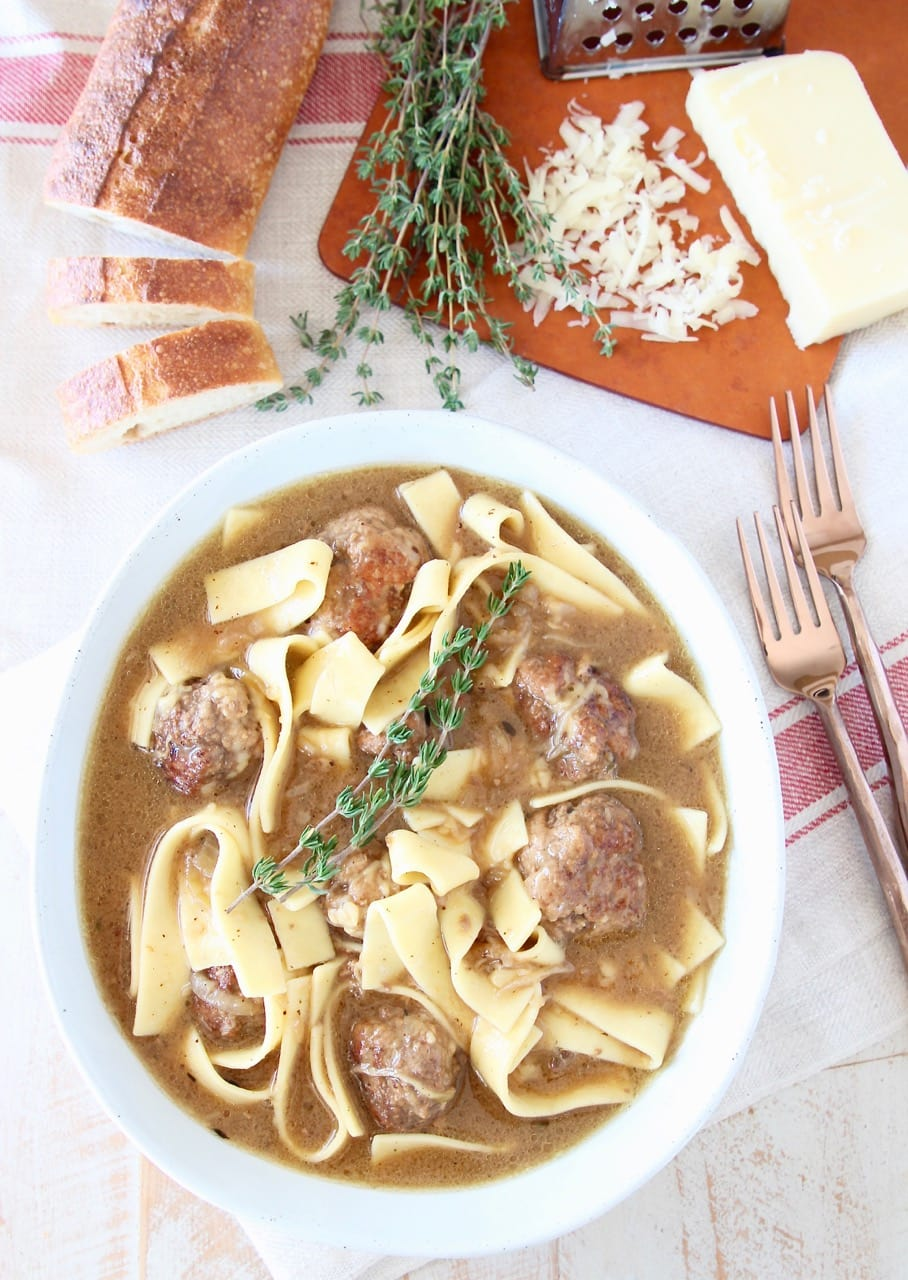 Bowl of egg noodles, meatballs and thyme sprigs on red striped towel with two copper forks and sliced baguette on cutting board