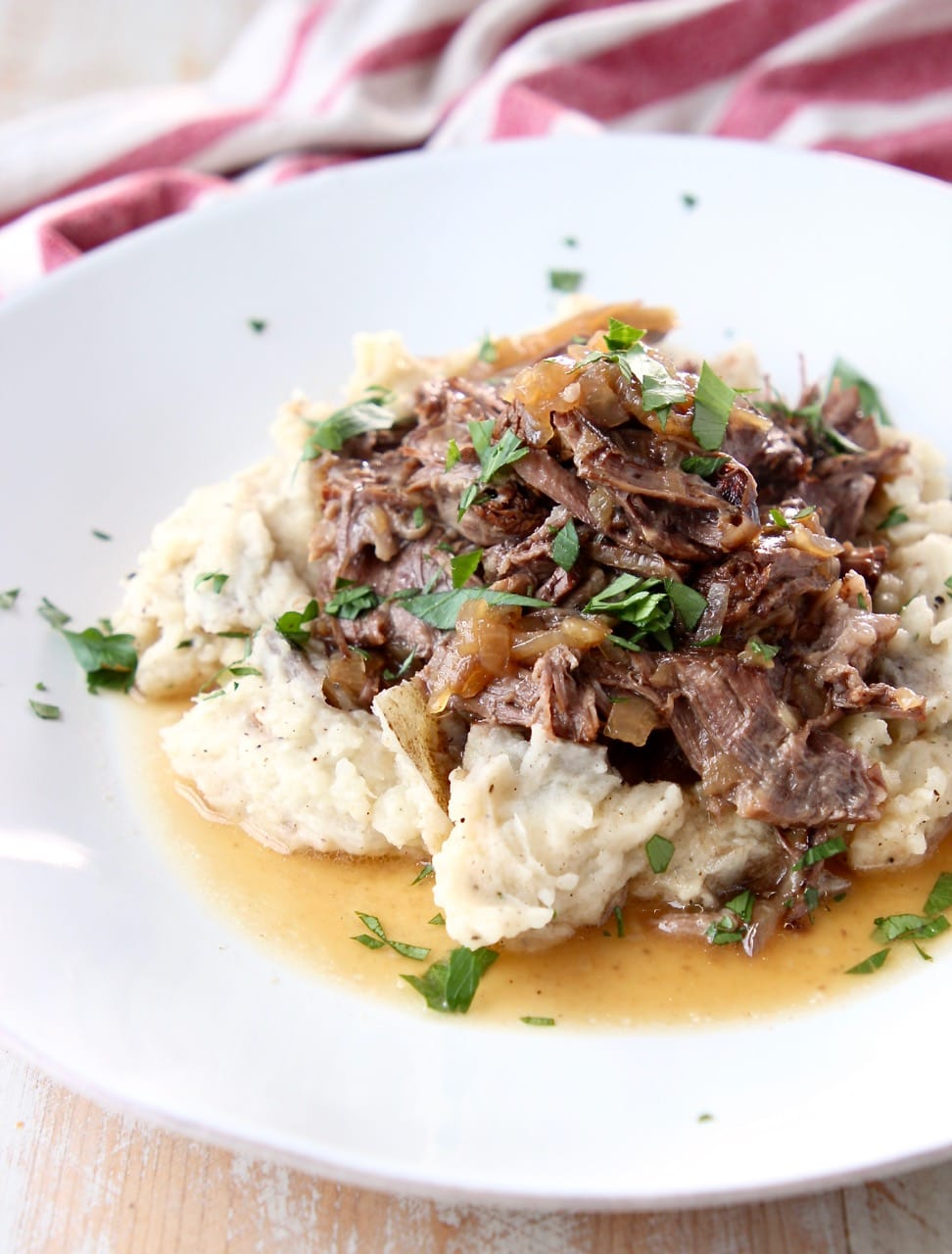 Shredded pot roast topped with fresh parsley on mashed potatoes on white plate with red and white towel