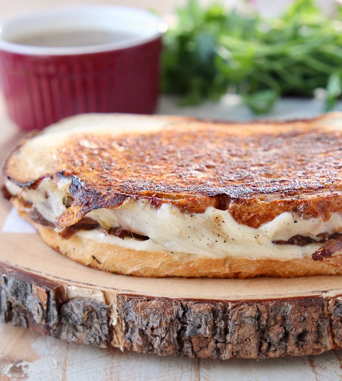 Pot roast grilled cheese sandwich with melted gruyere cheese on wood cutting board with fresh parsley and small red ramekin of au jus