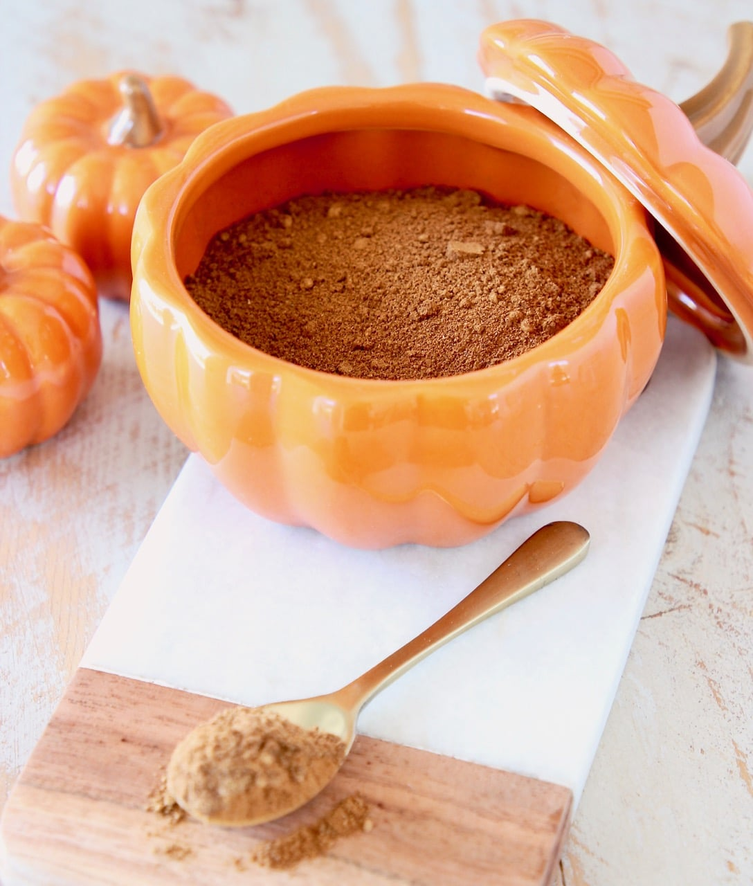 Pumpkin pie spice on small gold spoon on cutting board with ceramic pumpkin filled with pumpkin pie spice and two smaller orange pumpkins on the side
