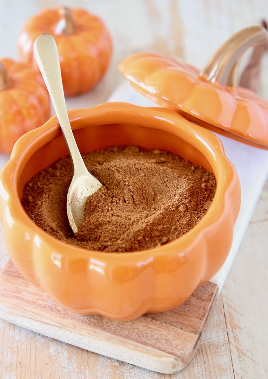 Homemade pumpkin pie spice in small orange pumpkin bowl with small gold spoon on marble cutting board