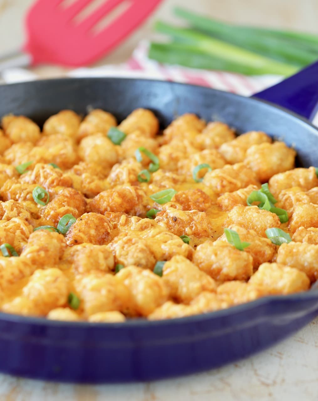 Tater Tot casserole with diced green onions in blue cast iron skillet with red spatula