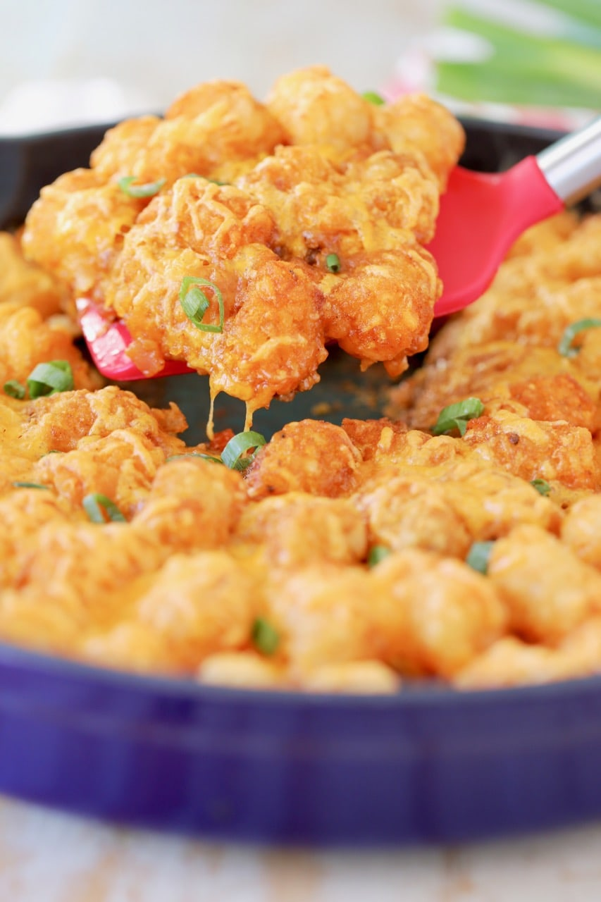 Buffalo cheeseburger tater tot casserole in blue cast iron skillet with red spatula lifting casserole out of skillet