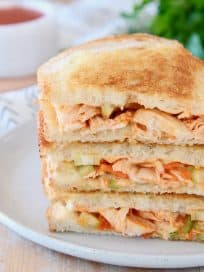 Buffalo turkey grilled cheese sandwiches, sliced in half diagonally, stacked up on white plate with fresh parsley in the background