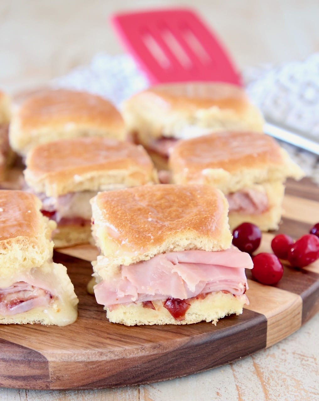 Ham sliders on hawaiian rolls with cranberry sauce, on wood cutting board with fresh cranberries on the side and red spatula in the background