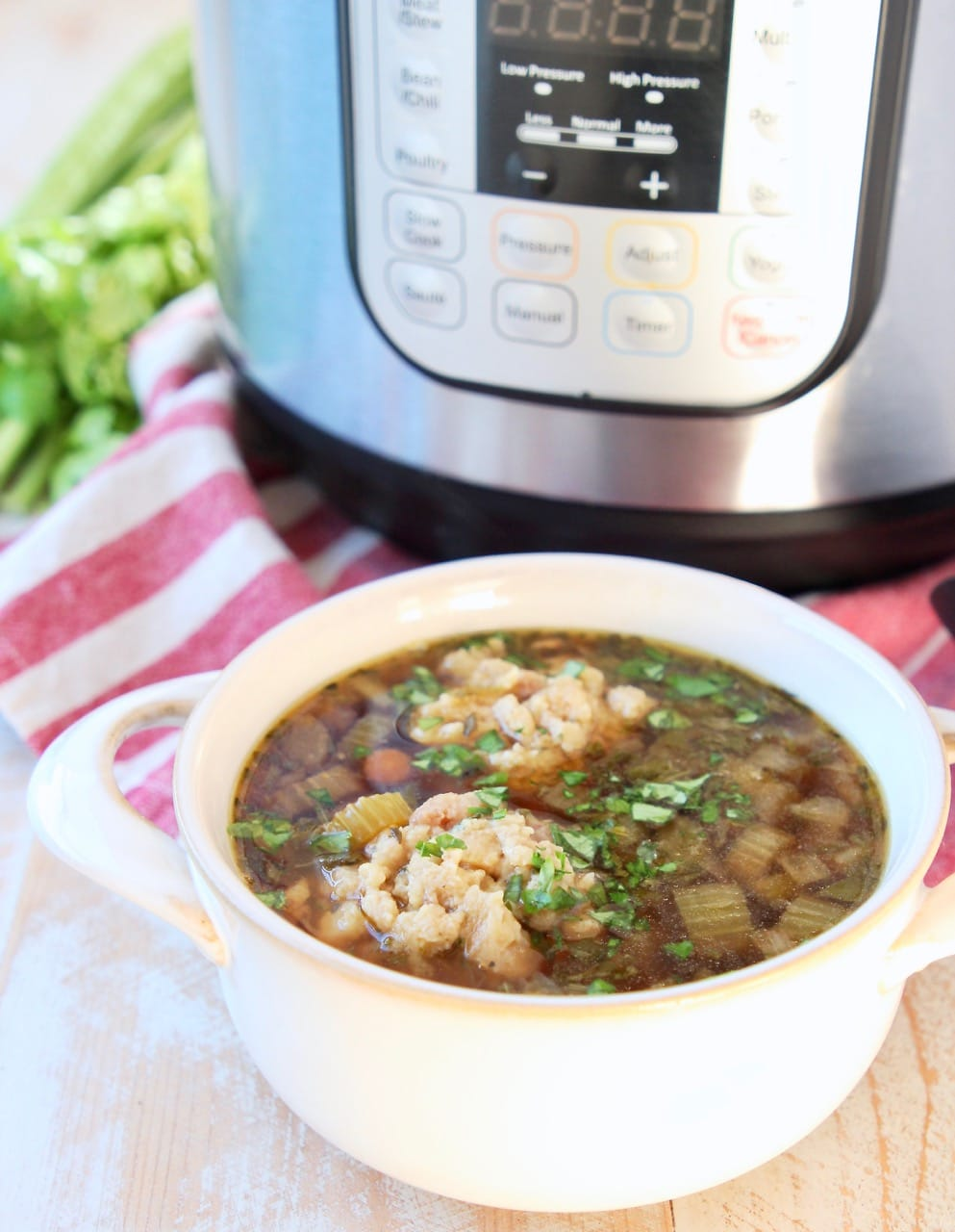 Instant Pot Turkey Soup in white crock with Instant Pot in background sitting on red and white striped towel with fresh celery stalks on the side