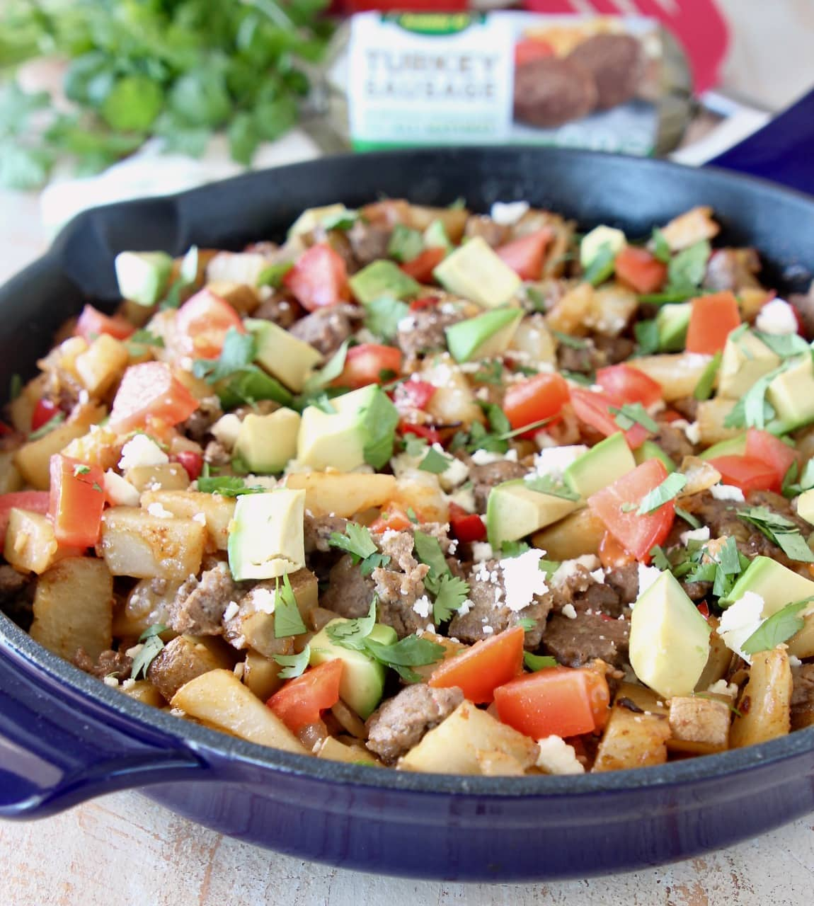 Potato hash in cast iron skillet with diced tomatoes, avocado and turkey sausage with fresh cilantro in background and roll of Jennie O Turkey Sausage