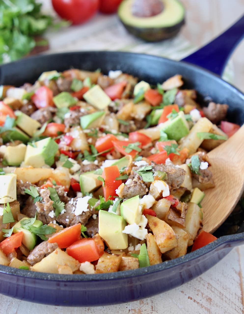 Breakfast hash in blue cast iron skillet with diced avocado, tomatoes, sausage and potatoes, with wooden spoon in skillet and fresh cilantro in background