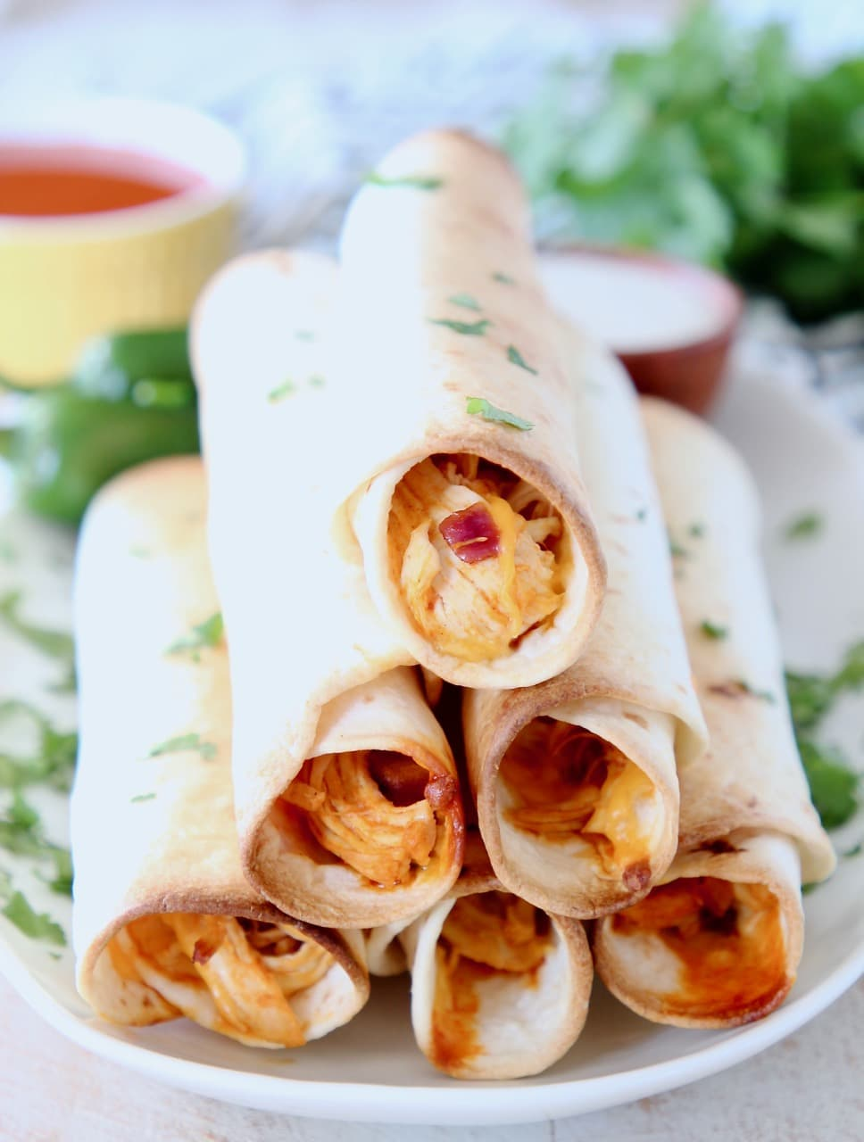 Buffalo chicken taquitos stacked up on plate with fresh cilantro and yellow ramekin of buffalo sauce in the background