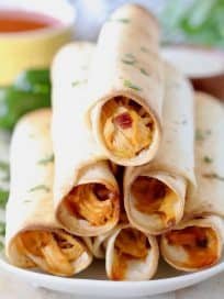 Buffalo chicken taquitos stacked on white plate with fresh cilantro garnish and jalapenos on plate in background