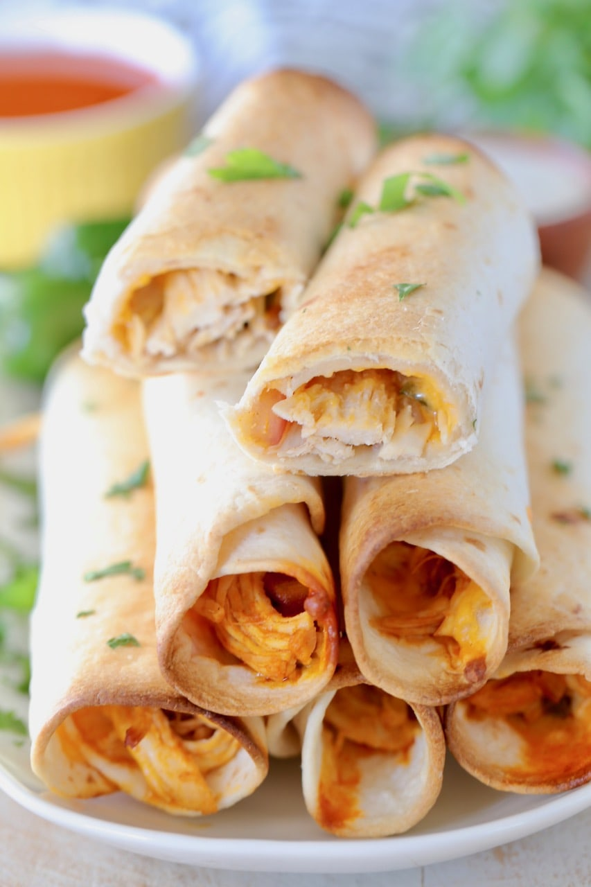 Baked buffalo chicken taquitos stacked up on a plate with the top taquito cut in half, garnished with fresh cilantro