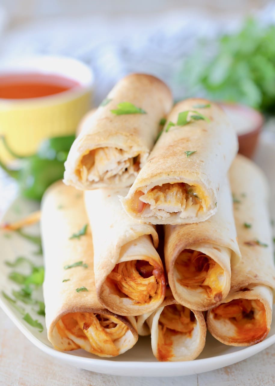 Buffalo chicken taquitos stacked up on plate with top taquito cut in half, garnished with fresh cilantro
