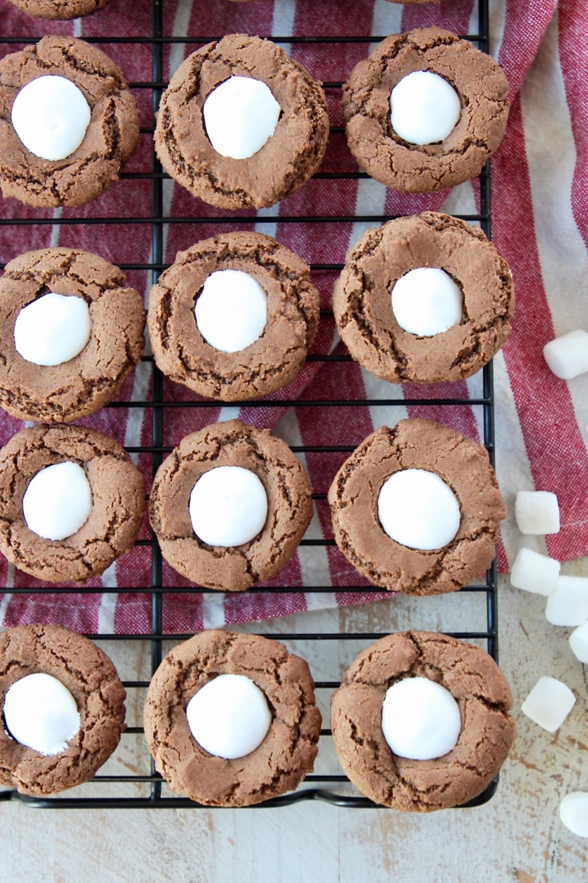Overhead shot of chocolate cookie cups filled with marshmallow creme on top of red and white striped towel with mini marshmallows on the side