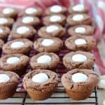 Hot chocolate cookie cups filled with marshmallow creme on black wire rack on top of red and white striped towel