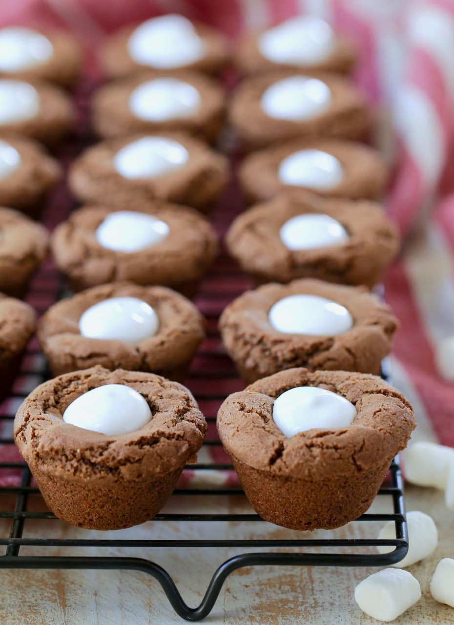 Hot chocolate cookies made into cups and filled with marshmallow creme on black wire rack with mini marshmallows on the side sitting on red and white striped towel