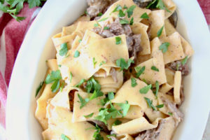 The Best Instant Pot Beef Stroganoff, picture of stroganoff with egg noodles in white serving bowl, image with text overlay
