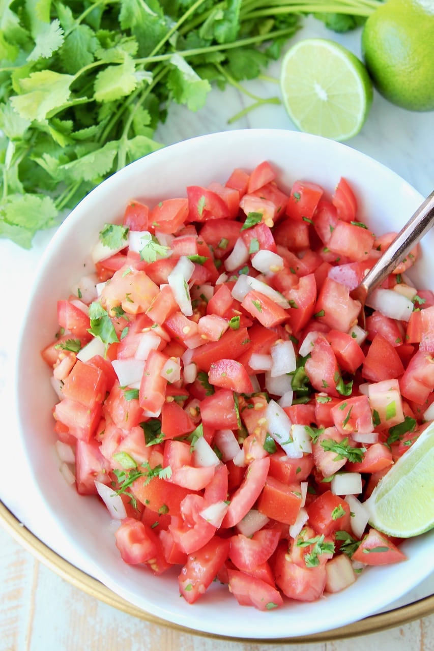 Overhead shot of pico de gallo in white bowl with fresh lime wedges and spoon in the bowl, with fresh cilantro on the side