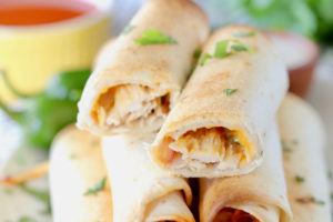 Stacked up baked buffalo chicken taquitos with text overlay