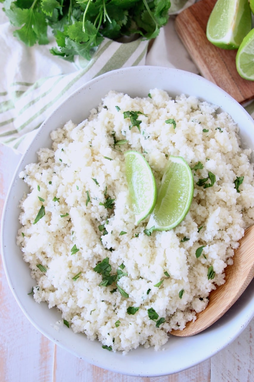 Large white bowl of cilantro lime cauliflower rice with two lime wedges on top and wooden spoon in the bowl