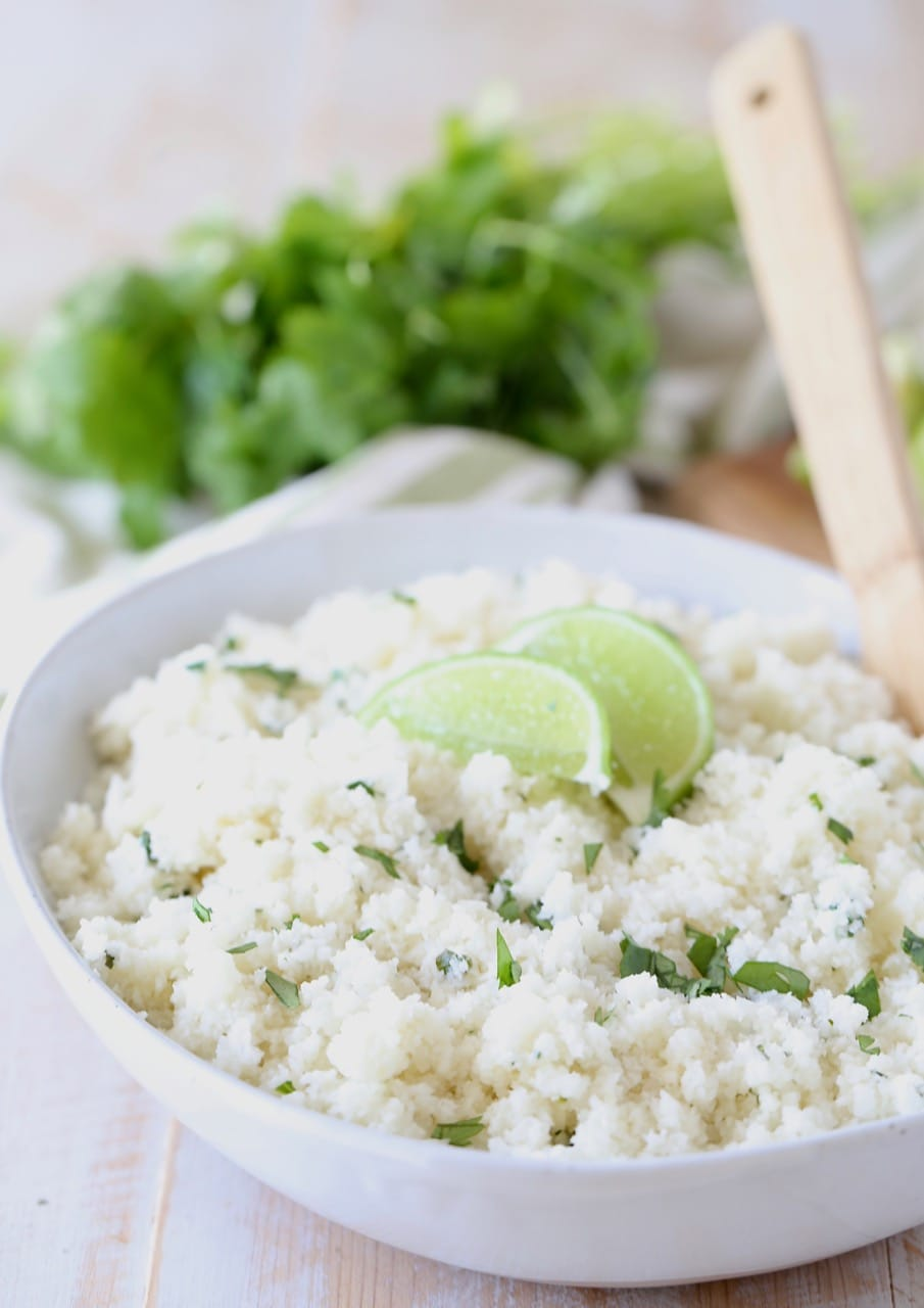 Cilantro lime cauliflower rice in white bowl with lime wedges on top and wooden spoon in bowl, with fresh cilantro in background
