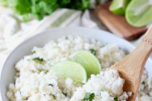 "Cilantro lime cauliflower rice in bowl in image with text overlay ""cilantro lime cauliflower rice, gluten free, keto, whole30, vegan"""
