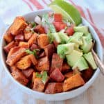 Diced roasted sweet potatoes in quinoa bowl with diced avocado, pico de gallo and lime wedge with copper fork