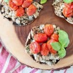 Overhead shot of stuffed portobello mushrooms filled with ground turkey, red cherry tomatoes and fresh basil leaves, sitting on a wood cutting board on top of a red and white striped towel