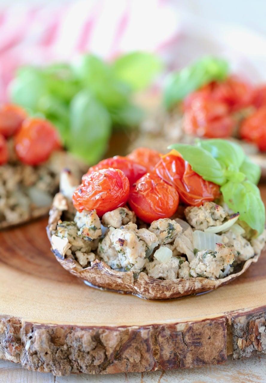 Stuffed portobello mushrooms with ground turkey, cherry tomatoes, fresh basil, on a wood cutting board