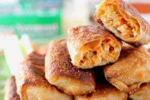 """Buffalo chicken egg rolls piled up on a green plate with one egg roll cut in half on top, with cheddar cheese and a cheese grater in the background with text overlay """"buffalo chicken egg rolls, quick & easy appetizer recipe"""""""