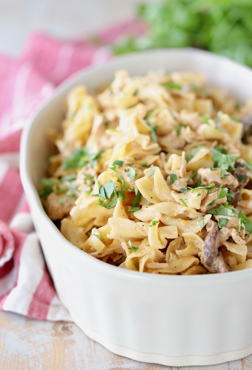 Chicken stroganoff with egg noodles in casserole dish with fresh parsley on top