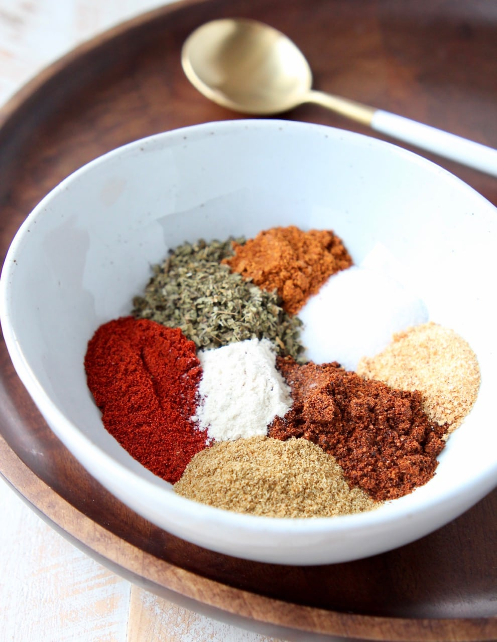 Fajita seasoning spices separated in white bowl on wood tray