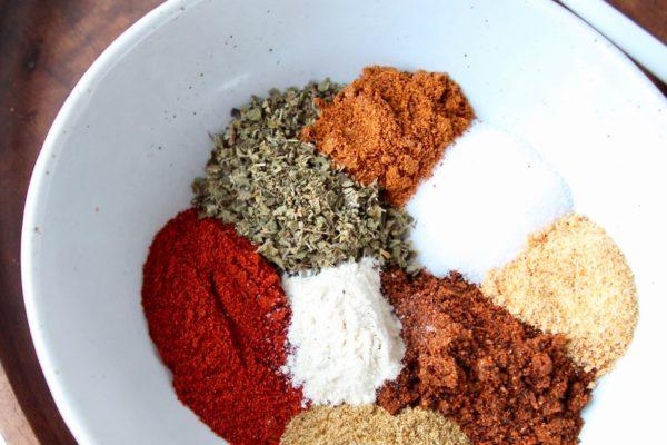 Fajita seasoning spices in white bowl on wood tray