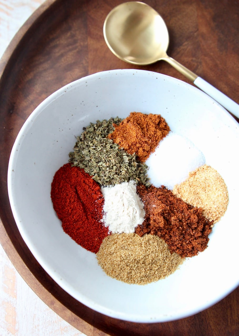 Fajita seasoning spices in white bowl on wood tray