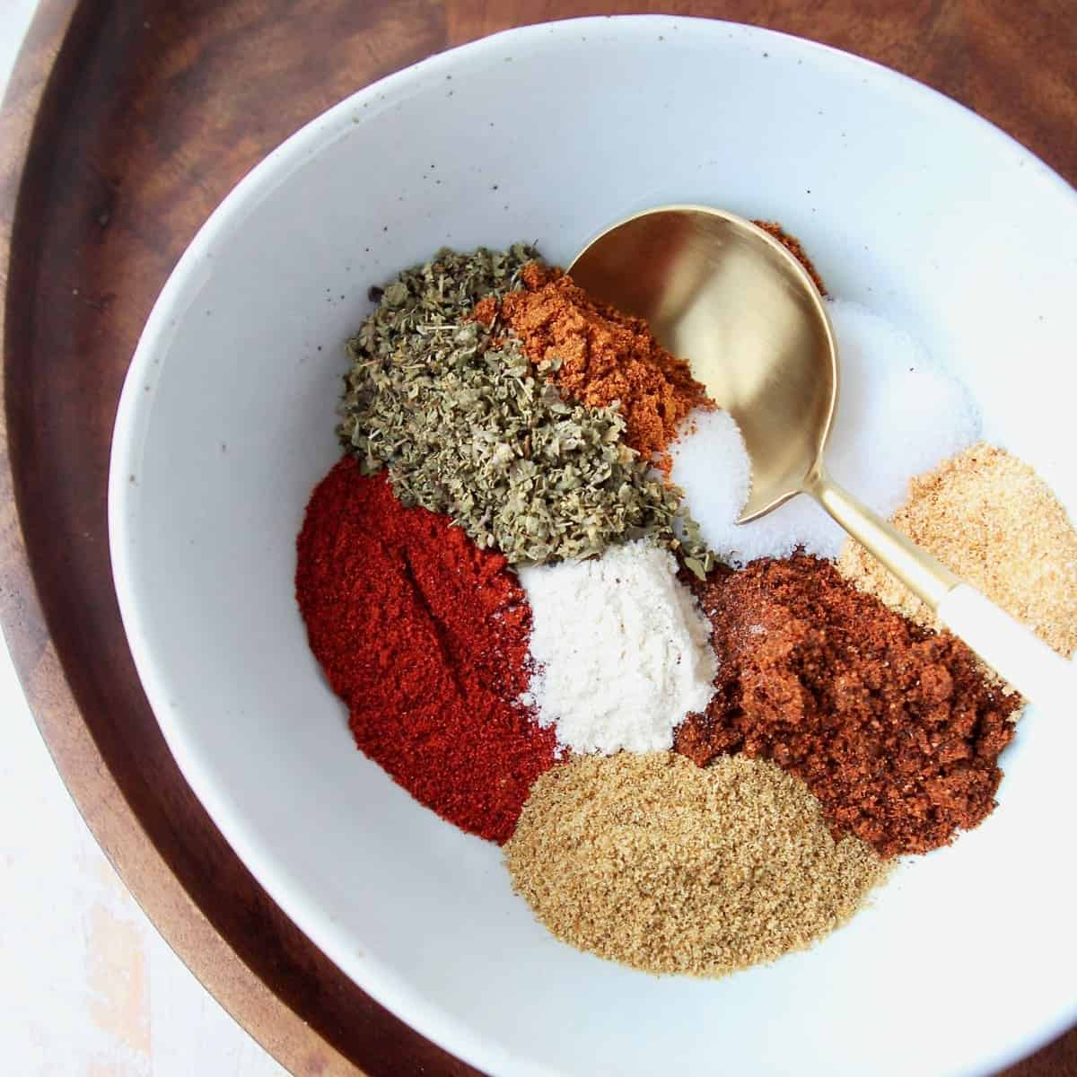 Fajita seasoning spices in white bowl with gold and white spoon in the bowl