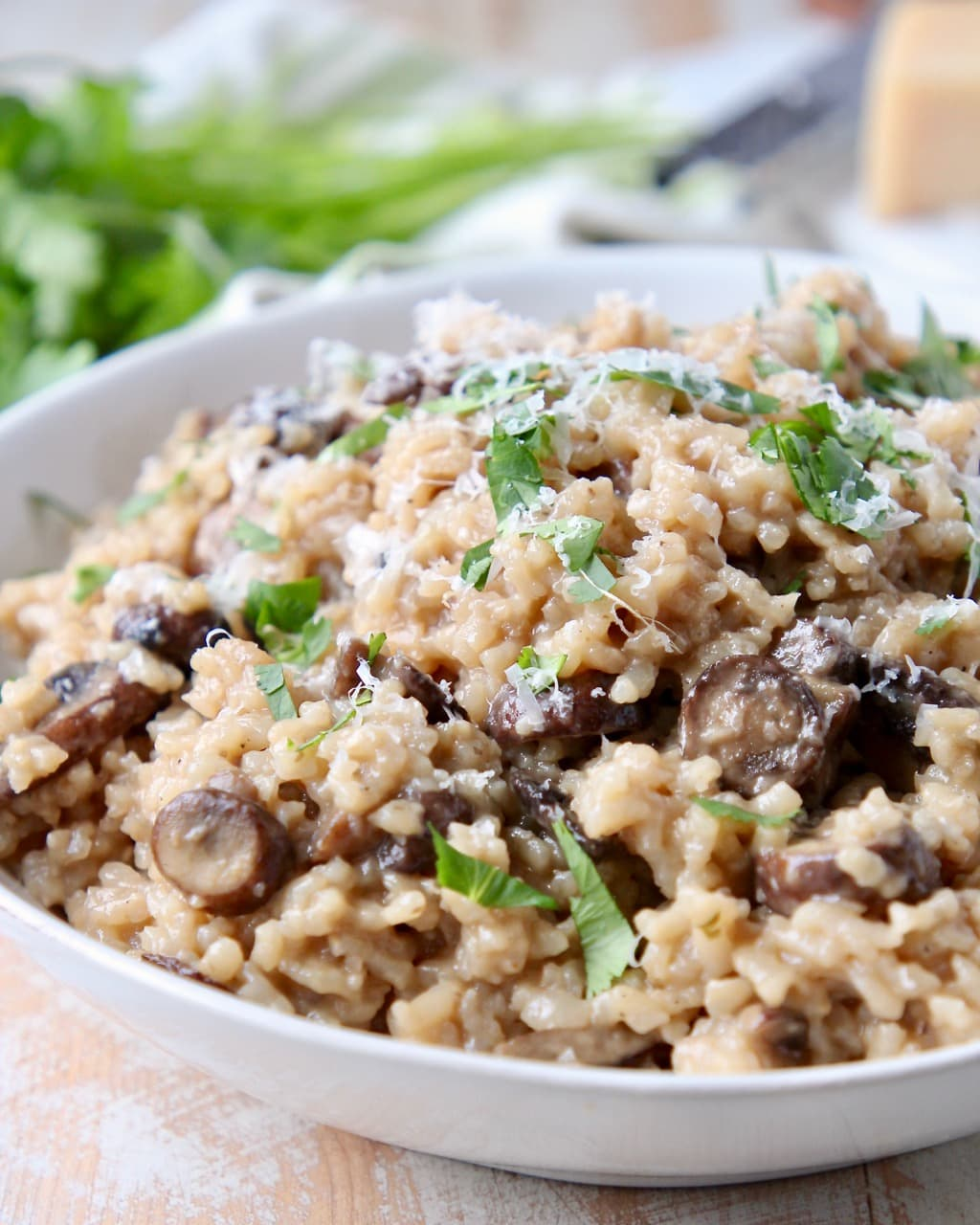 Instant pot mushroom risotto in bowl with fresh parsley and parmesan cheese