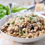 Mushroom risotto in bowl with parmesan cheese and spoon