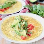 Avocado omelette topped with fresh basil, sliced avocado and fresh diced tomatoes