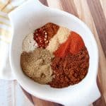 Eight spices for chili seasoning in a white bowl on a wood cutting board