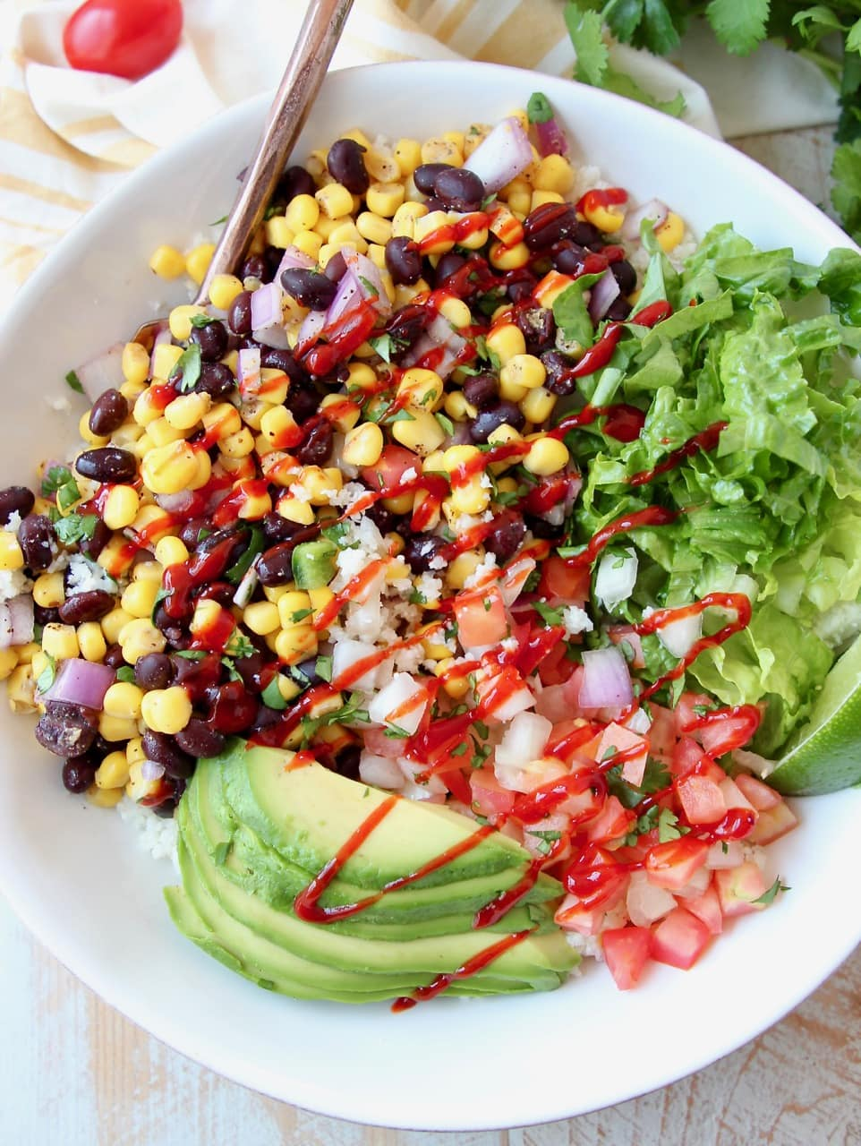 Burrito bowl with avocado, corn, tomatoes and black beans, topped with a drizzle of hot sauce in a white bowl