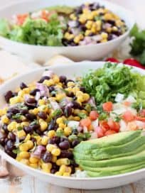 White bowl with sliced avocado, black bean and corn relish, diced tomatoes and shredded lettuce