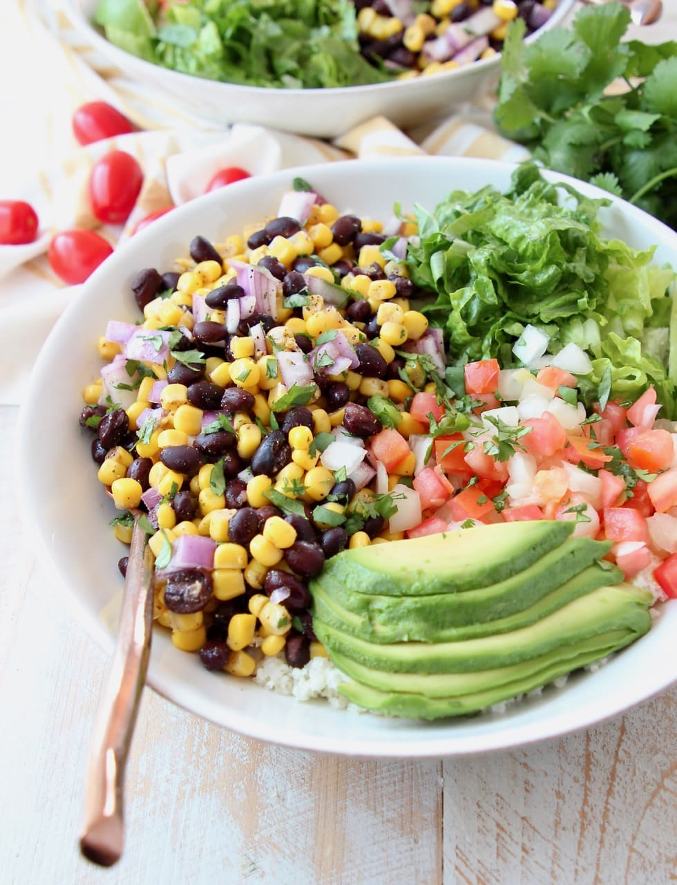 Vegan burrito bowl topped with avocado, black beans, corn, tomatoes and romaine lettuce